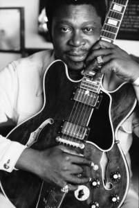 Portrait of jazz musician B.B. King holding his guitar.
